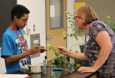 A 2018 OWjL camper studies plants with his teacher, OWU's Barb Wiehe.
